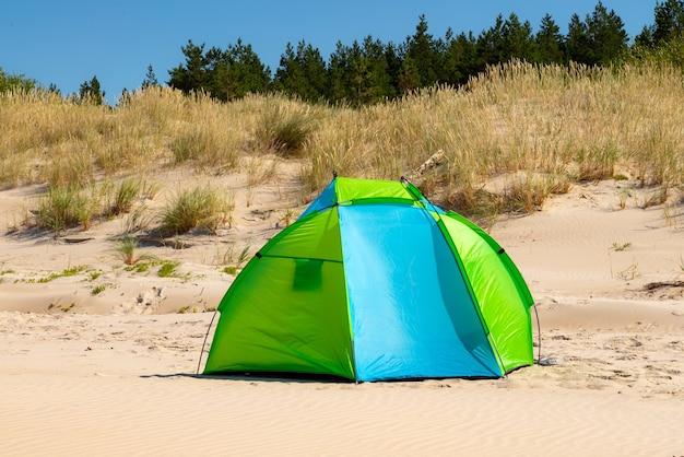 Namiot wiatrołapowy na piaszczystej plaży nad morzem.