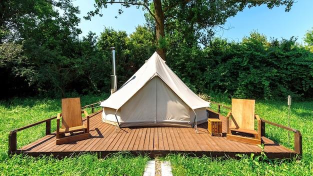 Namiot z drewnianymi krzesłami przed nim w glampingu. przyroda, zieleń wokół