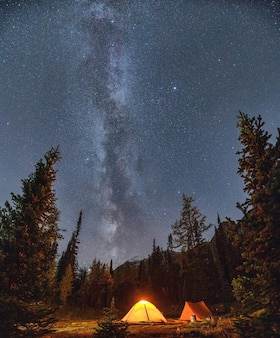 Namioty kempingowe z drogą mleczną i rozgwieżdżone na nocnym niebie na kempingu w jesiennym lesie w parku narodowym