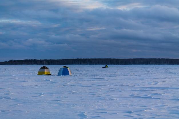Namioty wędkarskie na zamarzniętym i zaśnieżonym jeziorze