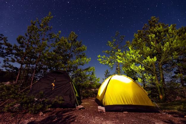 Namioty z płonącym światłem na tle rozgwieżdżonego nieba.