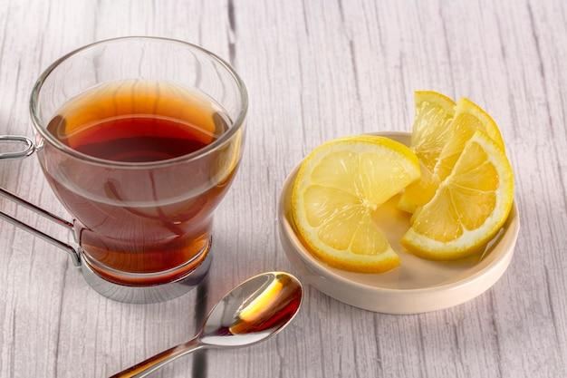 Napar w szkle na drewnianym stole w jasnych kolorach i białym tle plasterki cytryny i łyżeczka