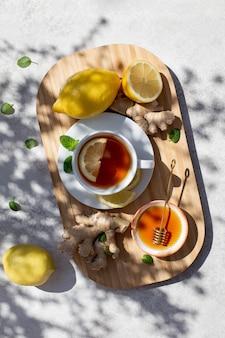 Napar z herbaty imbirowej w białej filiżance z plasterkiem cytryny, miętą, miodem