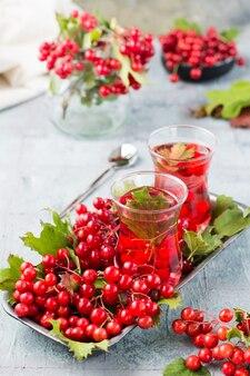Napar z jagód kaliny w szklankach i gałązkach z jagodami i liśćmi kaliny na podłożu na stole. medycyna alternatywna, wellness i odżywianie witaminami. widok pionowy