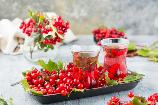 Napar z jagód kaliny w szklankach i gałązkach z jagodami i liśćmi kaliny na podłożu na stole. medycyna alternatywna, wellness i żywienie witaminowe