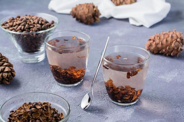 Napar z łupin orzeszków piniowych w szklankach i orzeszków piniowych na stole. medycyna alternatywna.