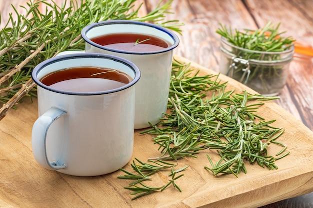 Napar z rozmarynu (rosmarinus officinalis). składnik kuchni śródziemnomorskiej i lecznicze domowe lekarstwo. rustykalny wygląd.
