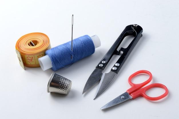 Naparstek, igła ze szpulą nici, nożyczki i taśma pomiarowa na białym tle .close-up.
