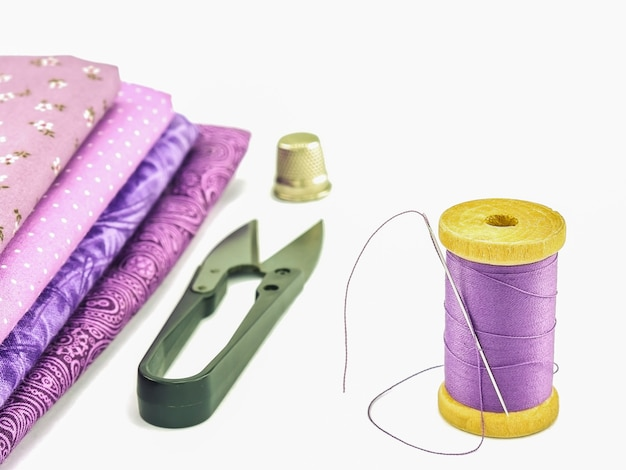 Naparstek, igły, szpule, nożyczki i tkaniny samodzielnie na białym tle