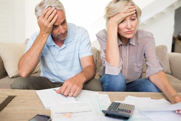 Napięta dojrzała para z rachunkami i kalkulator w domu