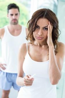 Napięta kobieta trzyma zestaw ciążowy podczas gdy mąż