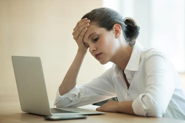 Napięta kobieta za pomocą laptopa w sali konferencyjnej