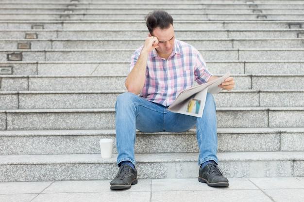 Napięta man reading gazeta na city stairway