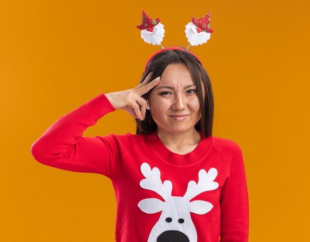 Napięta młoda azjatycka dziewczyna ubrana w świąteczny obręcz do włosów ze swetrem, kładąc palce na głowie na białym tle na pomarańczowej ścianie