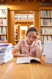 Napięta młoda kobieta studiuje w bibliotece