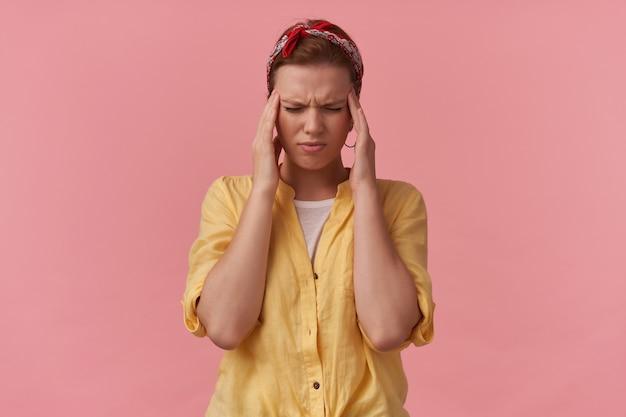 Napięta nieszczęśliwa młoda kobieta w żółtej koszuli z opaską na głowie i zamkniętymi oczami dotykająca skroni i mająca ból głowy na różowej ścianie
