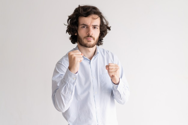 Napięte młody człowiek stojący w boksie pozować i patrząc na kamery