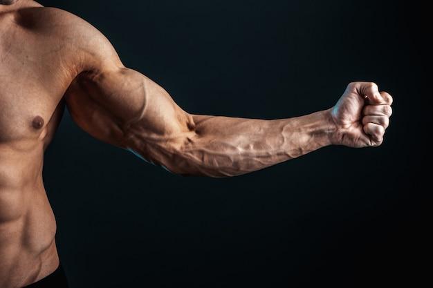 Napięte ramię zaciśnięte w pięść, żyły, mięśnie kulturysty na ciemnym miejscu, izolacja
