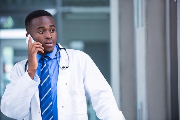 Napięty lekarz rozmawia przez telefon komórkowy