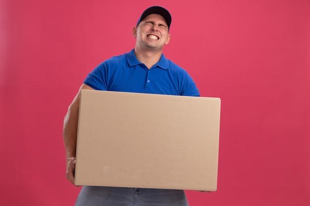 Napięty młody człowiek dostawy ubrany w mundur z czapką, trzymając duże pudełko na białym tle na różowej ścianie