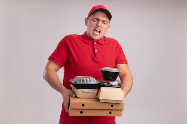 Napięty młody człowiek dostawy ubrany w mundur z czapką, trzymając pojemniki z żywnością na pudełkach po pizzy na białym tle na białej ścianie
