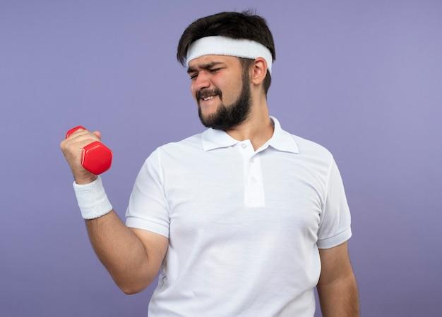 Napięty młody człowiek sportowy z opaską na głowę i nadgarstkiem, ćwiczenia z hantlami