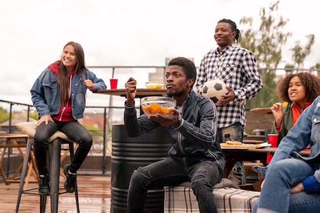 Napięty młody mężczyzna pochodzenia afrykańskiego z miską chipsów i jego przyjaciółmi oglądającymi transmisję meczu