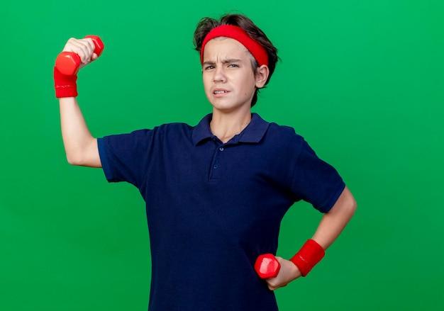 Napięty młody przystojny sportowy chłopiec noszący opaskę i opaski na nadgarstki z aparatami ortodontycznymi trzymający i podnoszący hantle patrząc z przodu odizolowany na zielonej ścianie z miejscem na kopię