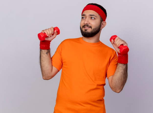 Napięty, młody sportowiec, patrząc na bok, noszenie opaski i nadgarstka ćwiczeń