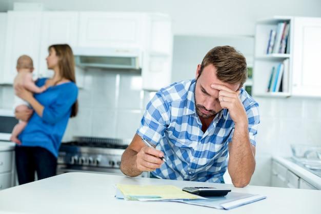 Napięty ojciec kalkulujący finanse domowe