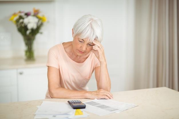 Napięty starszy kobieta siedzi w kuchni