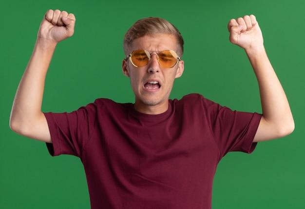 Napięty z zamkniętymi oczami młody przystojny facet ubrany w czerwoną koszulę i okulary podnosząc pięści na białym tle na zielonej ścianie