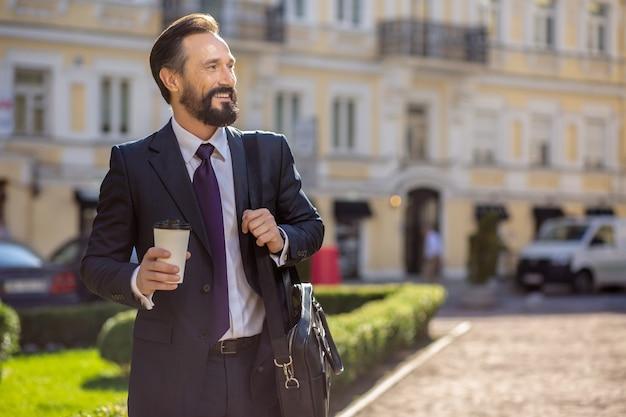 Napij się kawy. wesoły biznesmen uśmiechający się stojąc na zewnątrz, idąc do pracy