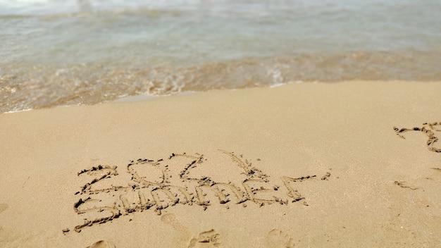 Napis 2020 2021 na piasku plaży. noworoczna koncepcja