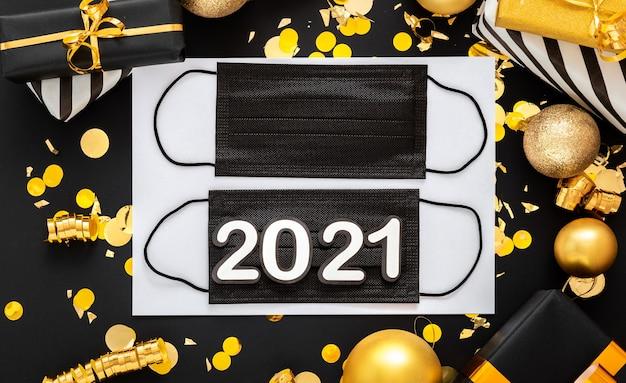 Napis 2021 na czarnych medycznych maskach na twarz ze złotym świątecznym wystrojem