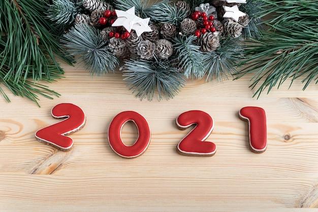 Napis 2021 z piernika z czerwoną glazurą i wieńcem bożonarodzeniowym. ścieśniać.