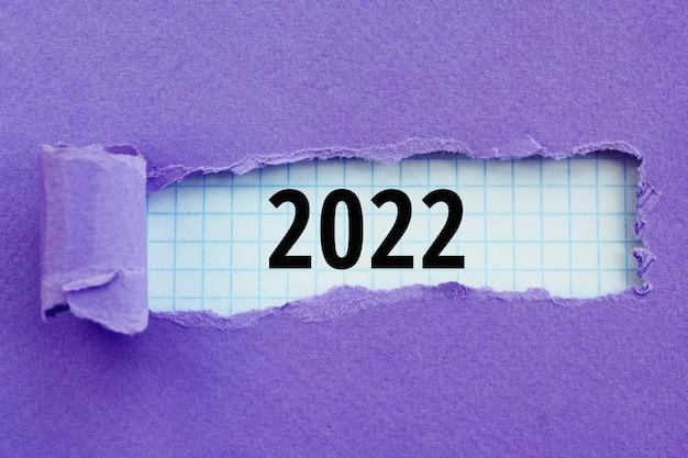 Napis 2022 w otworze z rozdartego fioletowego papieru. koncepcja rozpoczęła nowy rok 2022.
