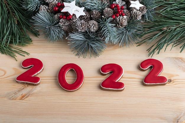 Napis 2022 z piernika z czerwoną glazurą i bożonarodzeniowym wieńcem. ścieśniać. drewniane tło.