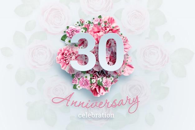 Napis 30 cyfr i tekst uroczystości rocznicowej na różowe kwiaty