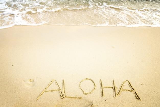 Napis aloha napisany na piaszczystej plaży z falą fal oceanicznych. vintage efekt kolorystyczny