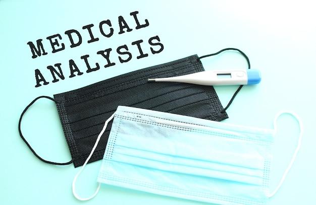 Napis analiza medyczna na niebieskim tle z leżącymi obok niebieskimi i czarnymi maseczkami medycznymi.