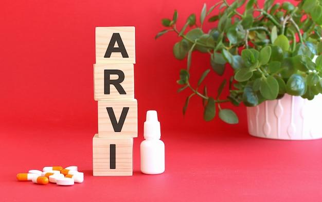 Napis arvi składa się z drewnianych kostek na czerwonym tle z lekarstwami.