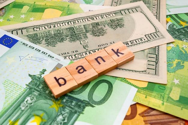 Napis bank na drewnianych kostkach na fakturze dolarów amerykańskich i banknotów euro