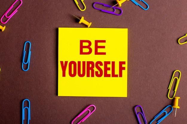 Napis be yourself jest napisany na czerwono na żółtej naklejce na brązowym tle obok wielokolorowych spinaczy do papieru