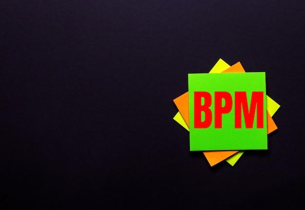 Napis bpm business process management na jasnej naklejce na ciemnym tle