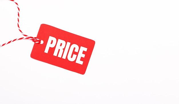 Napis cena na czerwonej metce na jasnym tle. koncepcja reklamy. skopiuj miejsce