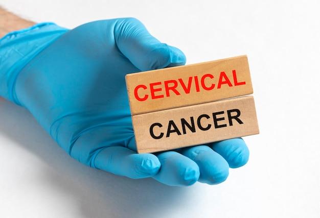 Napis choroby raka szyjki macicy na papierze w rękach lekarza w rękawiczkach, onkologia kobiet.