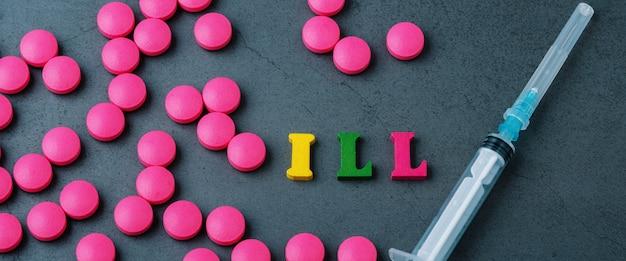 Napis chory na szarej powierzchni otoczonej porozrzucanymi tabletkami i strzykawką.