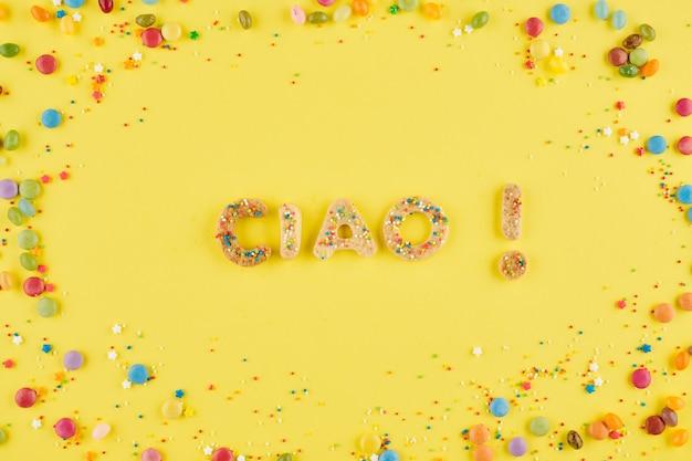 Napis ciao wykonany ze słodkich, domowych ciasteczek na żółtym tle z czekoladowymi cukierkami i kolorową posypką