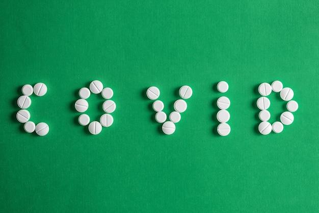 Napis covid 19 z liter składających się z tabletek na zielonym tle. koncepcja wirusa koronowego.